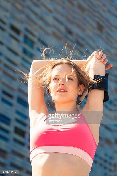 Beautiful athlete girl making stretching after intense run