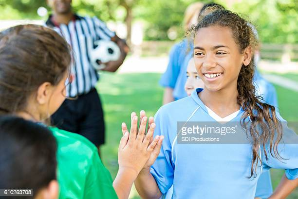 beautiful athlete gives opposing team high five after game - female umpire stockfoto's en -beelden