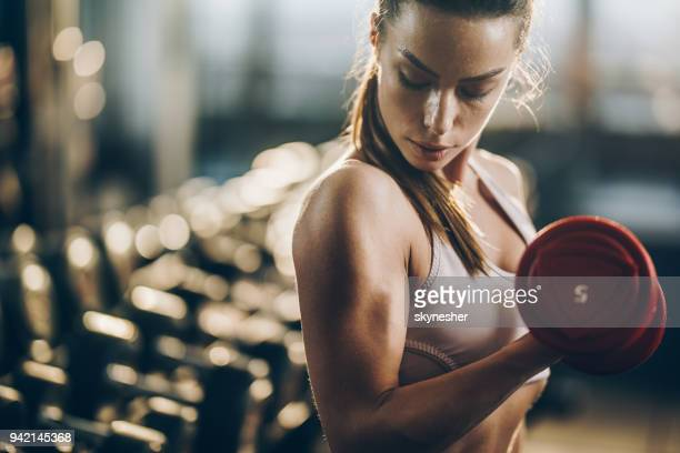 beautiful athletic woman exercising with dumbbells in a health club. - strength training stock pictures, royalty-free photos & images