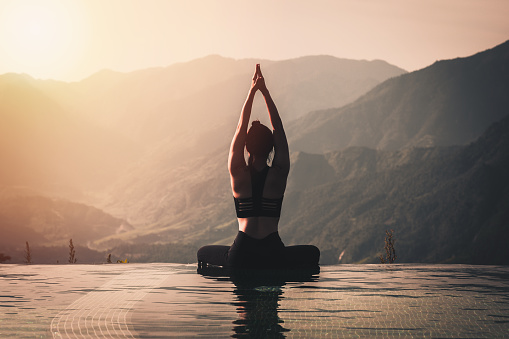 Beautiful Attractive Asian woman practice yoga Lotus pose on the pool above the Mountain peak in the morning in front of beautiful nature views,Feel so comfortable and relax in holiday,Warm tone 1074959548