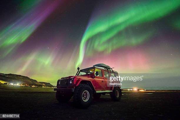 Beautiful aurora dancing over a red car.