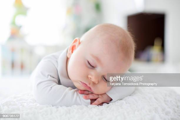 beautiful baby boy in white knitted cloths and hat, sleeping sweetly posed in bed - niños bebés fotografías e imágenes de stock