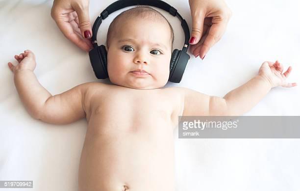 Hermoso bebé en toalla blanca con auriculares