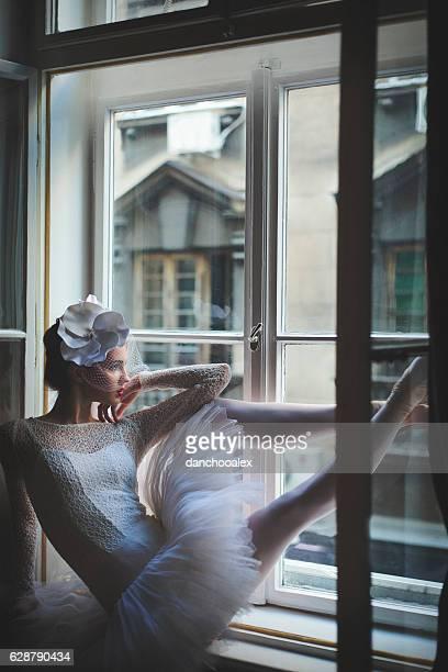 Beautiful balerina looking trough window