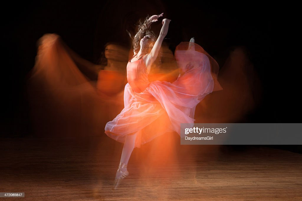 Beautiful Ballerina Dancing on Dark Stage with Ghosts : Stock Photo
