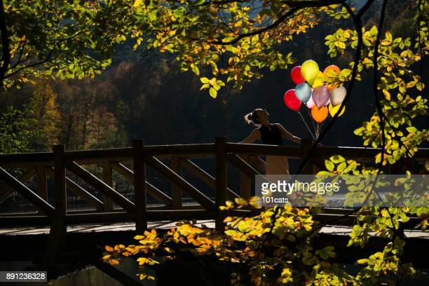 schöne Ballerina tanzen auf hölzernen Wharf in der Nähe des Sees in die Herbstsaison mit Farbe Luftballons