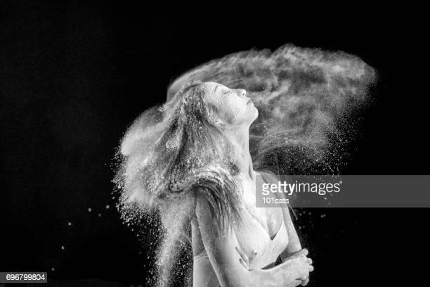 Retrato de la hermosa bailarina de baile bailando con polvo en el escenario