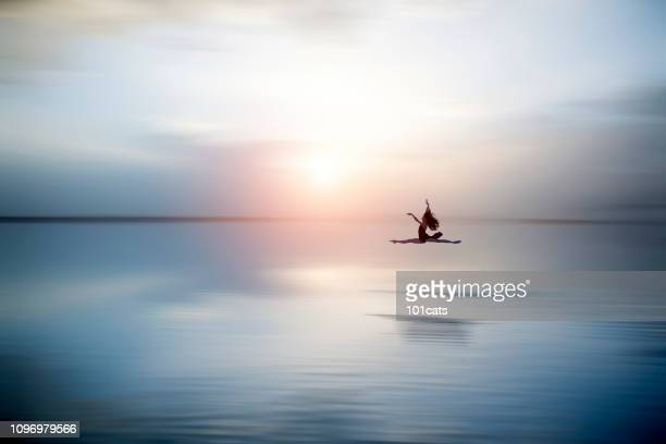 beautiful ballerine jumping and  dancing on the lake in the evening - spirituality stock pictures, royalty-free photos & images