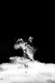 Beautiful ballet dancer, dancing with powder on stage