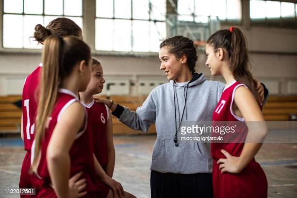 beautiful basketball coach with her team - sportsperson stock pictures, royalty-free photos & images