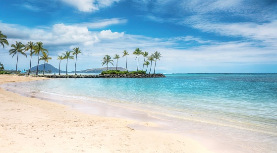 A beautiful beach scene in the Kahala area of Honolulu, with fine white sand, shallow turquoise water, a view of coconut palm trees and Diamond Head in the background. 1078914728
