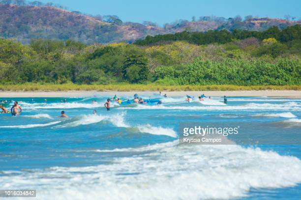 beautiful beach scenery at playa tamarindo, guanacaste - costa rica - medium group of people stock pictures, royalty-free photos & images