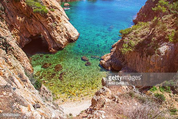 Beautiful beach with crystal waters between crags and hole in the Mediterranean Costa Brava on summertime.