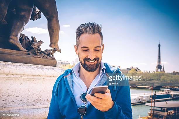 Wunderschöne bärtiger Touristen, die mit Handy auf Pont Alexandre in Paris