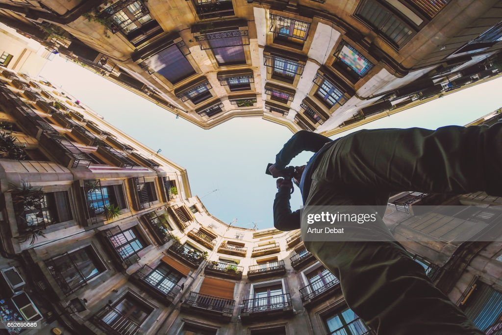 Beautiful below view with wide angle lens taken from the ground and looking  up of tourist traveler taking pictures and contemplating the beautiful  streets ...
