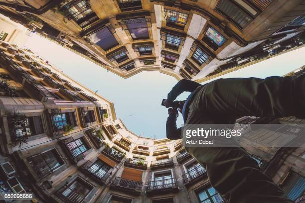 Beautiful below view with wide angle lens taken from the ground and looking up of tourist traveler taking pictures and contemplating the beautiful streets of gothic quarter in Barcelona city with narrow street and nice round square.