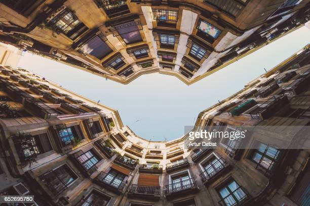 Beautiful below view with wide angle lens taken from the ground and looking up of the beautiful streets of gothic quarter in Barcelona city with narrow street and nice round square.