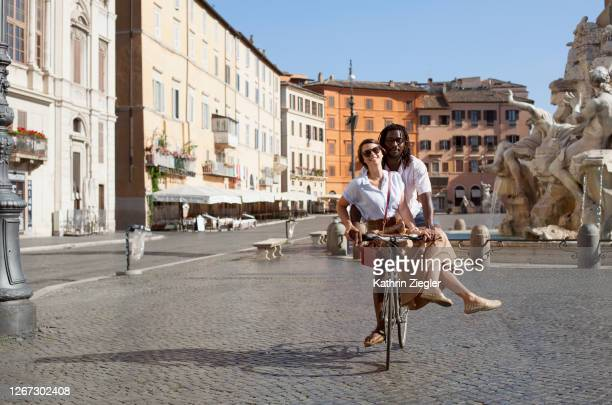beautiful biracial couple riding bicycle in deserted piazza navona, rome, italy - europa meridionale foto e immagini stock