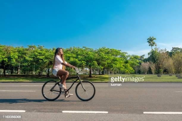 mulher brasileira preta bonita que monta uma bicicleta - ciclismo - fotografias e filmes do acervo