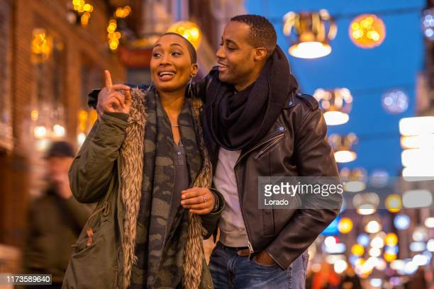 beautiful black couple at christmas shopping - heterosexual couple stock pictures, royalty-free photos & images