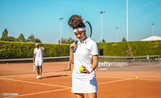 a beautiful black female tennis player on the court with her coach father - tennis tournament stock pictures, royalty-free photos & images