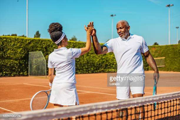 a beautiful black female tennis player on the court with her coach father - country club stock pictures, royalty-free photos & images