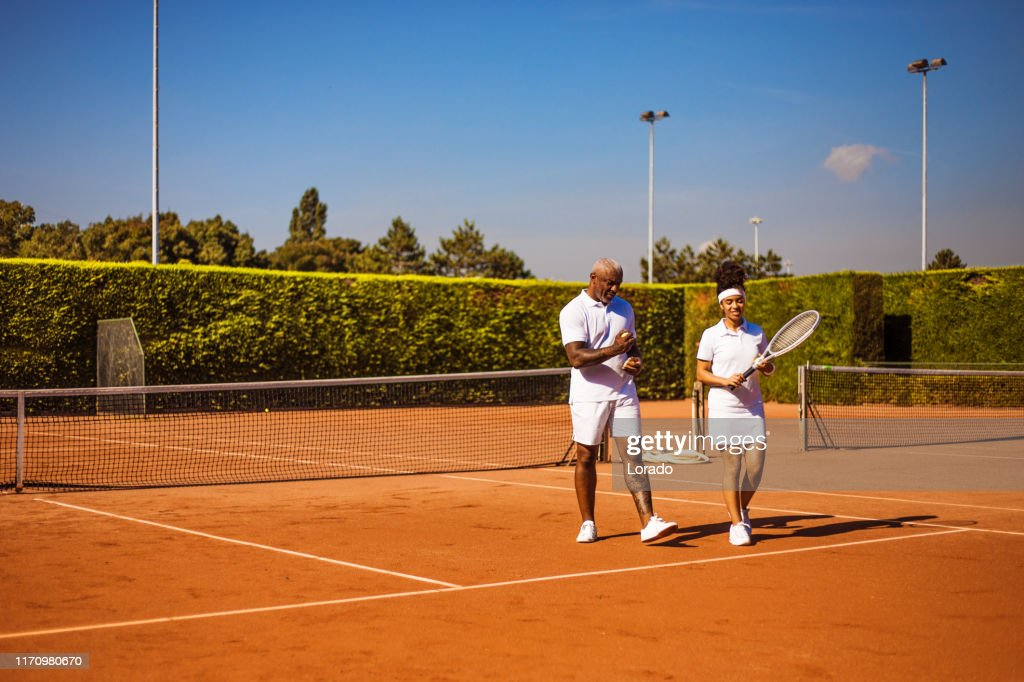 A beautiful black female tennis player on the court with her father and coach : Stock Photo