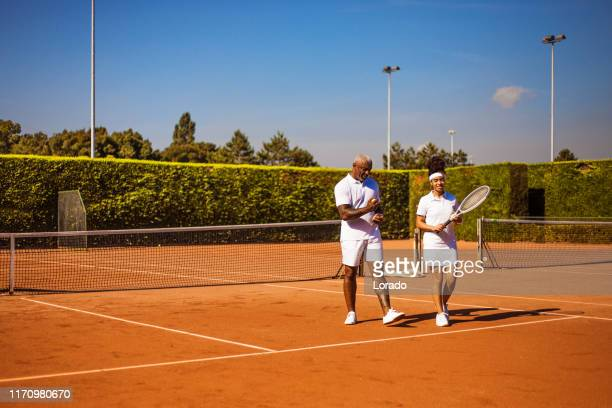 a beautiful black female tennis player on the court with her father and coach - sports training drill stock pictures, royalty-free photos & images