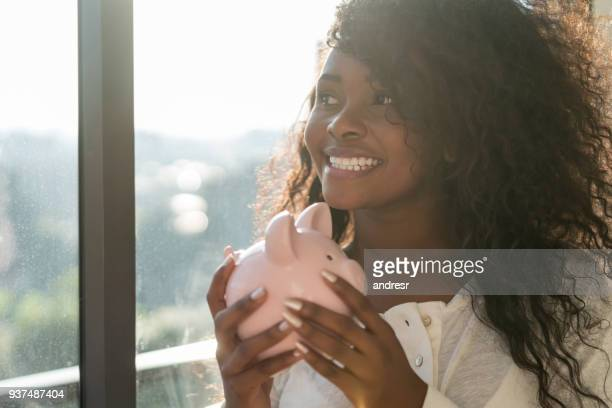 Beautiful black latin american woman holding her piggy bank daydreaming next to the window