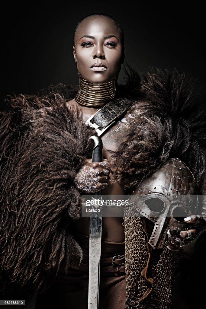 Beautiful black warrior princess holding a sword in studio shot : Stock Photo