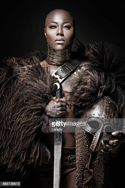 beautiful black warrior princess holding a sword in studio shot - warrior person stock photos and pictures