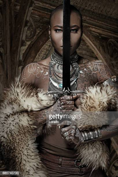 beautiful black warrior princess holding a sword in studio shot - mulher guerreira imagens e fotografias de stock
