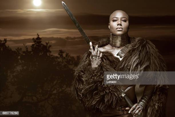 Beautiful black warrior princess holding a sword in studio shot