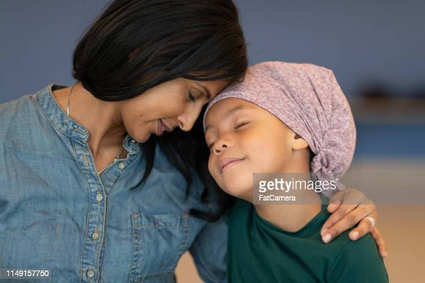 beautiful black woman affectionately embraces young daughter with cancer - chronic illness stock photos and pictures