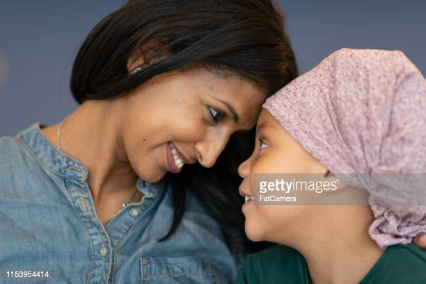 beautiful black woman affectionately embraces young daughter with cancer - affectionate stock pictures, royalty-free photos & images