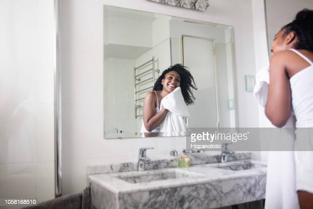 Beautiful black woman drying her face with a towel while looking at herself in the mirror smiling