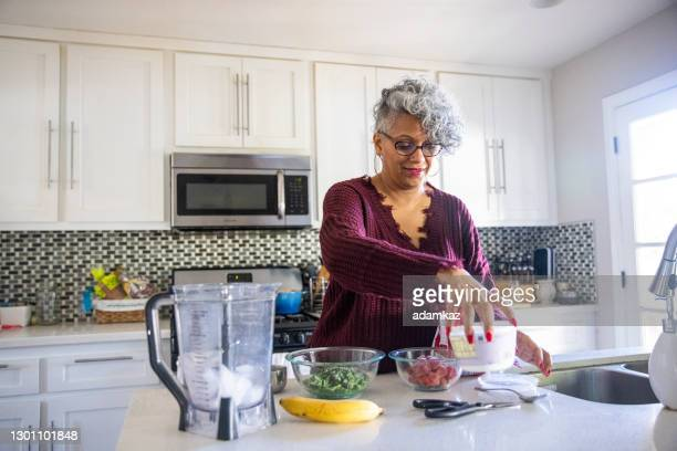 beautiful black woman having a smoothie - fat nutrient stock pictures, royalty-free photos & images