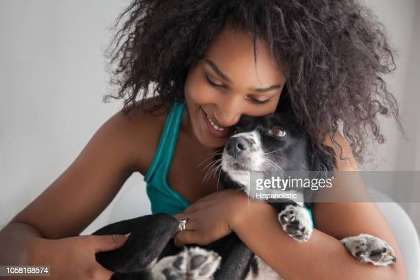 beautiful black woman hugging her mixed breed dog while she smiles - mixed breed dog stock pictures, royalty-free photos & images