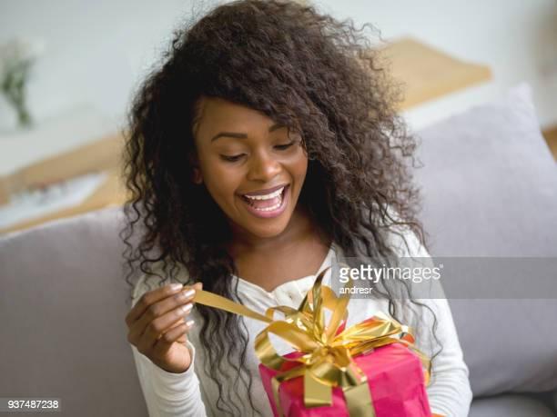 Beautiful black woman opening a birthday gift while sitting on the couch at home looking excited