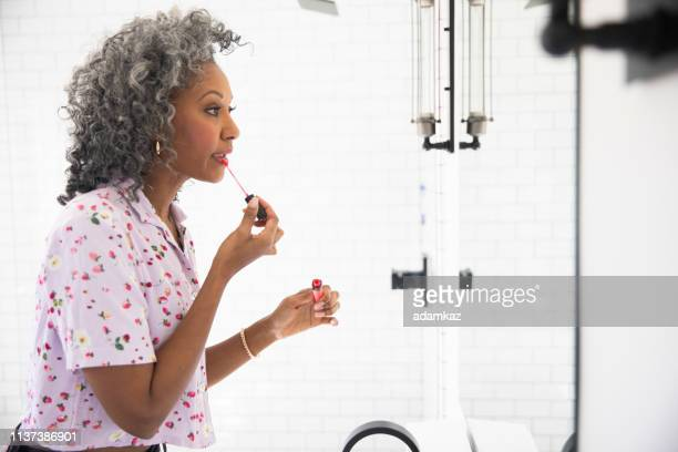 beautiful black woman putting on makeup - lip gloss stock pictures, royalty-free photos & images
