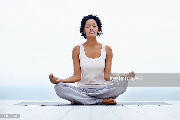beautiful black woman sitting in lotus position outdoors - lotus position stock pictures, royalty-free photos & images