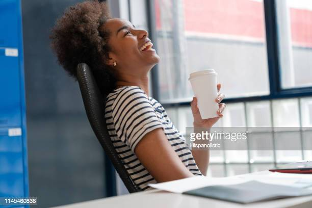 beautiful black woman taking a break sitting on chair at the office enjoying a coffee and laughing - hispanolistic stock photos and pictures