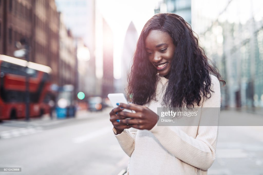 Beautiful black woman using phone in downtown to call crowdsourced taxi : Stock Photo
