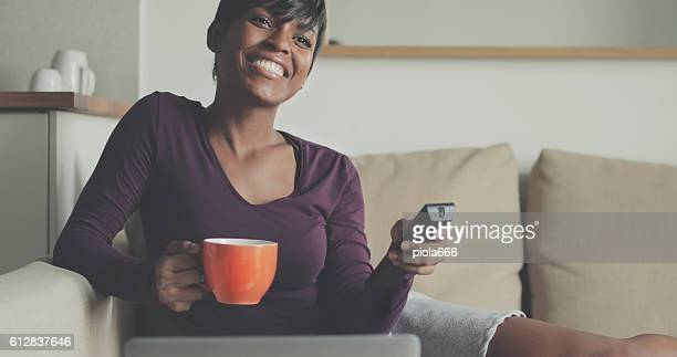Beautiful black woman watching TV at home
