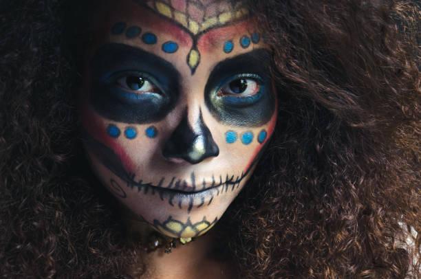 Beautiful black woman with Halloween sugar skull make up, smiling.