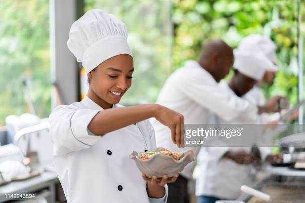 beautiful black woman working at a restaurant cooking - food and drink industry stock photos and pictures