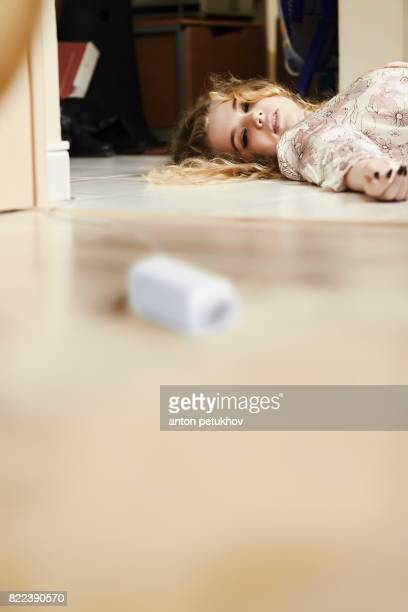 Beautiful blond girl lies on the floor in the room.