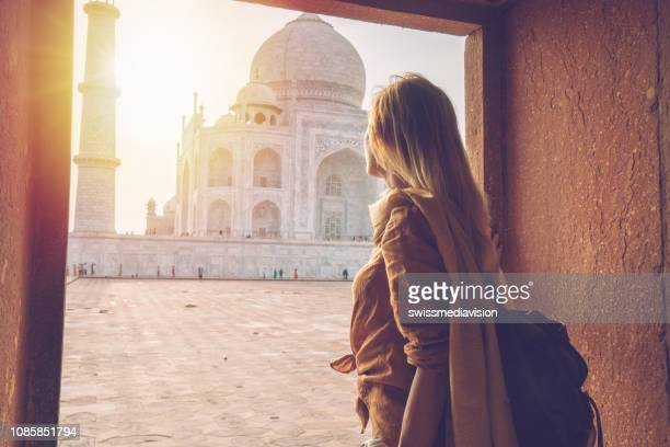 beautiful blond hair girl contemplating sunrise at the taj mahal in india - india stock pictures, royalty-free photos & images