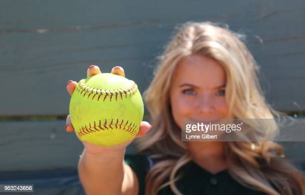 beautiful blond holds a yellow softball - softball sport stock pictures, royalty-free photos & images