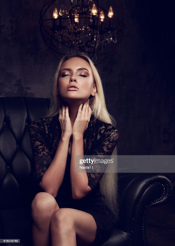 Beautiful blond mystical woman spelling sitting on armchair : Stock Photo